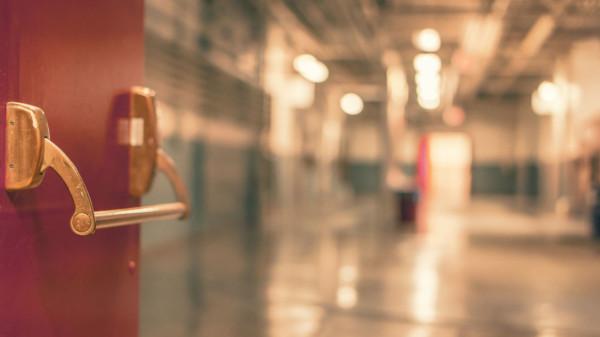 Das Bild zeigt verschwommen eine Krankenhaustür mit Flur